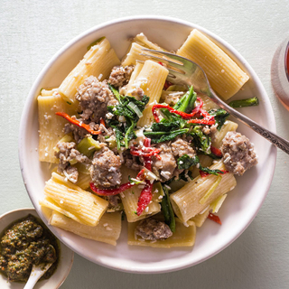 rigatoni pasta with sausage, leeks and broccoli rabe on top in a white bowl with a fork