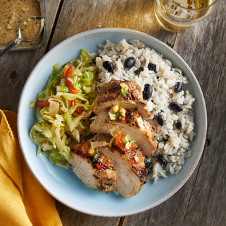 Jerk chicken breast sliced into four slices with white rice and black beans and pineapple slaw on a wooden table.