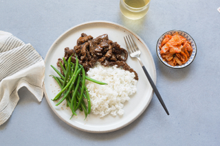 korean bbq beef with sticky white rice and green beans on a white dinner plate with a black fork