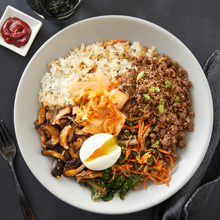 Korean bibimbap beef bowl with white rice, ground beef and a poached egg and vegetables on a white plate with a side of red-hot sauce in a small square dish.
