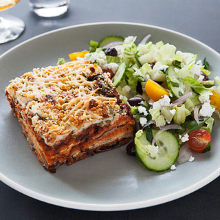 Side view of a square slice of moussaka topped with browned bechamel sauce next to a fresh green salad with cucumbers and chopped tomatoes on a grey plate.