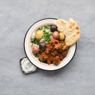 black plate with steamed white rice and lamb vindaloo with carrots and peas and fresh naan