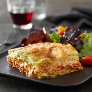 slice of pesto lasagna on a black plate with a side salad and a glass of red wine.