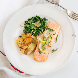 White round dinner plate with roasted lemon basil salmon, crispy sliced potatoes and cooked greens on a white background with a silver fork.