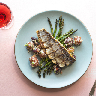 seared branzino fillet on a plate with asparagus and potato salad