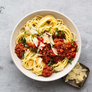 Lentil bolognese with linguine pasta in a white bowl on a light concrete background with a side of shaved cheese in a small dish.