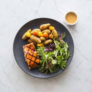 black plate with maple-bourbon glazed grilled salmon fillet, roasted potatoes and green salad