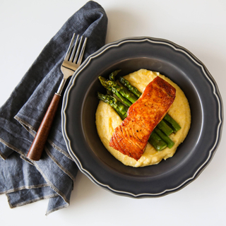 maple glazed salmon over yellow corn and cheddar grits and asparagus on a black plage