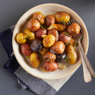 White bowl of roasted whole potatoes with fresh rosemary and a fork and spoon on the side.