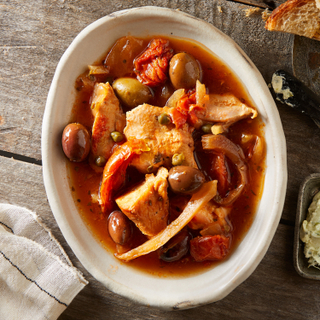 Mediterranean braised chicken pieces with olives, sliced peppers and onions in broth in a white bowl on a wooden table with toasted bread on the side.