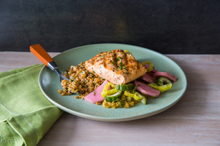 Mediterranean grilled salmon on a teal plate with farro and middle eastern pickles with an orange fork on the side.
