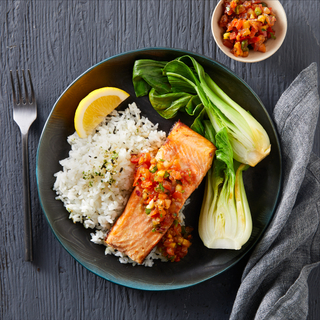 Black ceramic bowl with white rice, cooked bok choy halves and a salmon fillet topped with lomi-lomi tomatoes on a black wooden table.