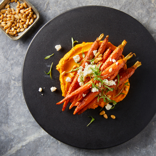 Roasted whole carrots on a bed of carrot hummus topped with cheese and pine nuts on a black round plate.