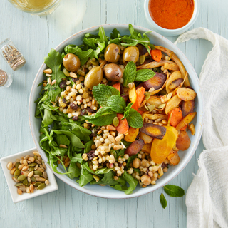 White bowl with Moroccan vegan grain bowl with greens, olives, carrots and grains on a white wooden background with red sauce on the side.