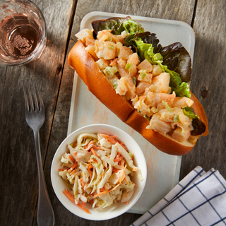 Rectangular white dinner plate with a New England style shrimp roll on a hot dog bun with a bowl of crunchy slaw on a wooden table top with a glass of rose and a checkered napkin.