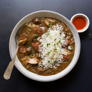 white bowl of Creole style gumbo with chicken and sausage with white rice and hot sauce