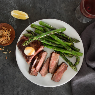 White bowl of New York strip steak sliced into five pieces with green asparagus on a dark background with a glass of red wine and a lime wedge on the wide.