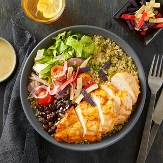 Dark round bowl filled with chicken taco salad with cilantro-lime rice, chopped greens, tomatoes, black beans and sliced chicken breast served with a drink with a lemon inside.