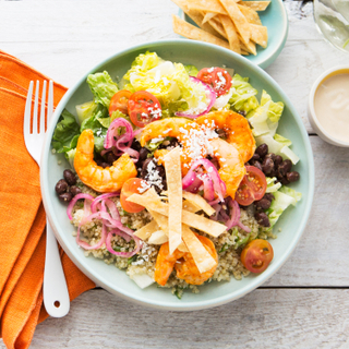 Green bowl filled with shrimp taco salad with colorful vegetables, crispy tortilla strips and roasted shrimp next to a folded orange napkin with a fork on a white table.