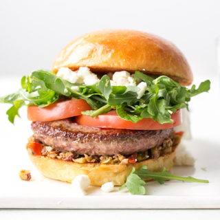 Side view of olive and feta lamb burger on a brioche roll with sliced tomato, greens and crumbled feta cheese on top.