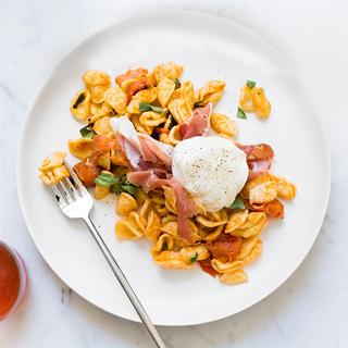 orecchiette pasta with prosciutto and cheese on a white plate