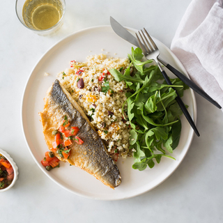 Seared sea bass fillet over couscous salad with olive, peppers and capers and arugula on the side on a white dinner plate