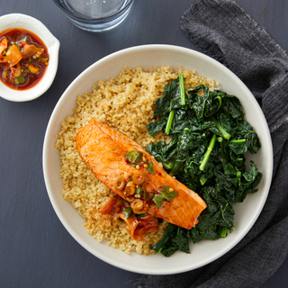 White dinner plate with quinoa, sauteed greens and pan-seared fillet of salmon with chunky pickled ginger dressing on top and in a dish on the side.