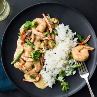 panang curry shrimp with white rice and vegetables in a black bowl
