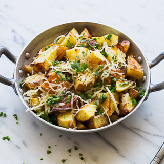 Parmesan roasted potatoes in a metal dish with handles topped with cheese and green herbs on a white marble table.