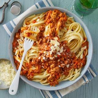 fettuccine pasta with bolognese sauce and shredded cheese in a round bowl with a fork on top
