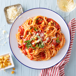 Pasta pomodoro with red sauce in a white and blue bowl topped with shaved cheese and fresh herbs over a red and white striped napkin.