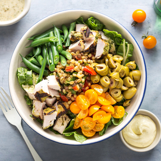 bowl with green beans, chopped chicken breast, cherry tomatoes and green olives with salad greens
