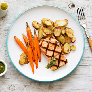 grilled salmon fillet with roasted potatoes and carrots on a white round dinner plate on a wooden table