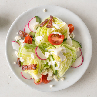 Petite iceberg wedge salad with sliced tomatoes, radishes, and bacon on a white round table on a white background.
