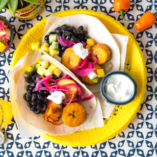 Bright yellow late with two tortillas holding sliced plantains, black beans, pickled red onions and diced mango salsa with a side of sour cream on a blue patterned background with three orange peppers on the side.
