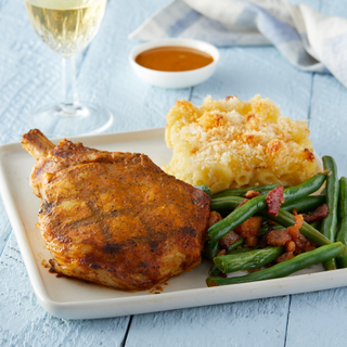 Square white plate with spiced grilled pork chop next to a square of mac and cheese with a crispy top and green beans with bacon in front of a glass of white wine on a white wooden table top.