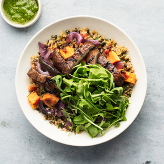 Portobello mushroom and pesto grain bowl with fresh greens, sweet potato and red onions in a white bowl with green sauce in a dish on the side.