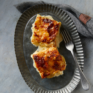 Two square slices of potato gratin with a browned top on a galvanized tin plate with a fork on the side.