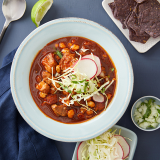 bowl of red pork pozole with sliced radishes and crunchy green cabbage