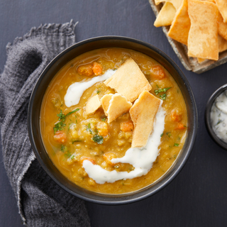 Red lentil soup topped with crisp naan and tzatziki sauce in a black bowl on a black background with a dark linen napkin.