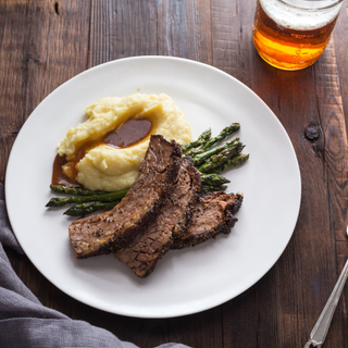 slices of red wine braised beef brisket with mashed potatoes and roasted asparagus on a white dinner plate
