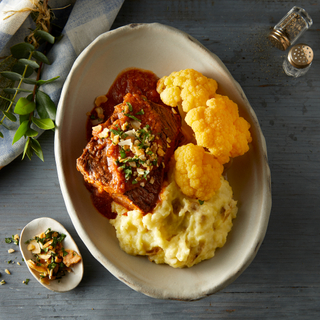 Oblong plate with red wine braised short ribs, golden cauliflower florets and creamy mashed potatoes topped with almond picatta.