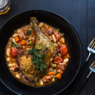 roasted chicken leg with cajun beans and tomatoes in a black bowl