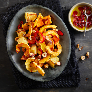 Roasted mixed fall squash pieces on a dark stone plate with crushed hazelnuts and pomegranate seeds on top on a black cloth.