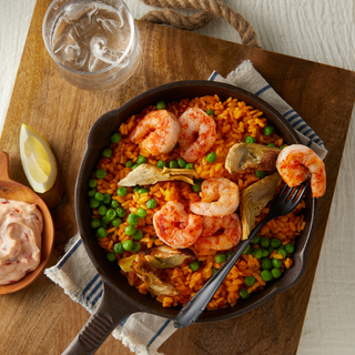 Cast iron skillet with saffron rice topped with roasted shrimp with a black fork on top on a wooden board on a wooden tabletop.