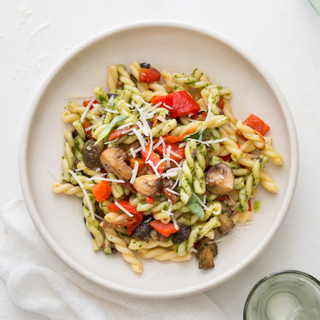 Roasted vegetable pesto pasta with curly noodles, red vegetables and green sauce on a round white plate with three glasses around the plate and a white napkin.