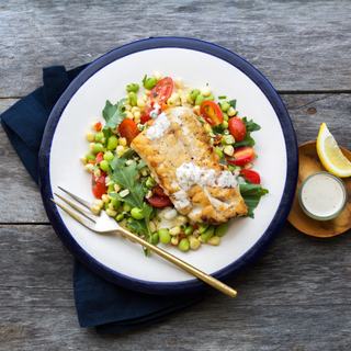 white plate with grilled cod with corn succotash on a wooden background with lemon and sauce on the side