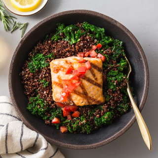 Dark bowl filled with black quinoa and greens and a grilled salmon fillet topped with red sauce. Next to a blue and white striped napkin on a white background with rosemary sprigs and fresh lemon on the side.