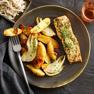 Brown dinner plate with roasted salmon fillet with green sauce next to crispy potato wedges and roasted sliced fennel with a fork.