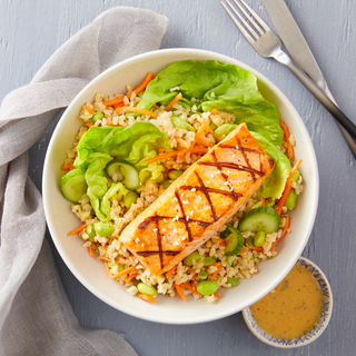 Salmon fillet over brown rice in a bowl with lettuce, cucumbers on a grey background with a napkin and fork.